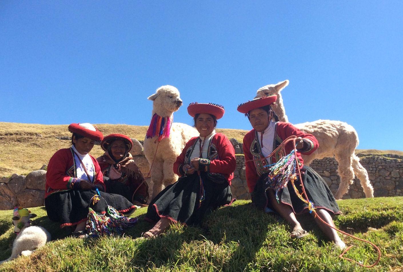 Mujeres con ropa tradicional junto a llamas